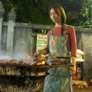 A THAI WOMAN GRILLS CHICKEN AT A ROADSIDE STALL (SOI RAMBUTRI : BANGLAMPHU DISTRICT) – IMAGE CREDIT KARIN RIIKONEN