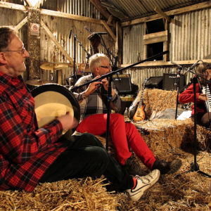 Members of a local band play traditional music upon a hay stage. Copyright Amy Laughinghouse.